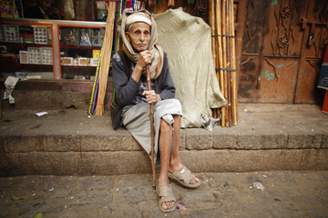 A man sits outside a shop at a marketplace in Old Sanaa city