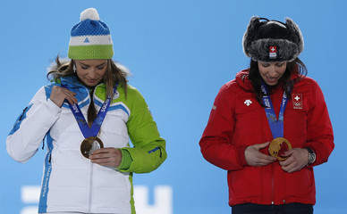 Joint gold medalists Switzerland's Gisin and Slovenia's Maze look at their medals during the medal ceremony for the women's alpine skiing downhill race at the Sochi 2014 Winter Olympic Games in Sochi