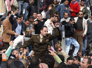 Protesters welcome a soldier during a demonstration in Cairo