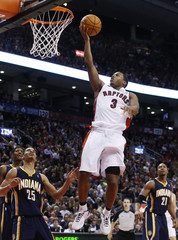 Toronto Raptors Kyle Lowry goes to the basket against Indiana Pacers Gerald Green and David West during their NBA basketball game in Toronto