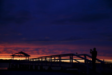 A man is silhouetted as he takes a photo during sunset on Manhasset Bay in Port Washington, New York