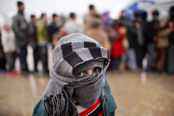 A boy walks past a queue of Syrian refugee waiting to receive aids from Turkish humanitarian agencies at Bab al-Salam refugee camp in Syria near the Turkish border