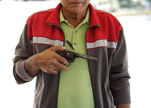 """A 58-year old man holds a 22 mm calibre gun before turning it in during the """"Voluntary Disarmament Programme"""" in San Nicolas in Monterrey"""