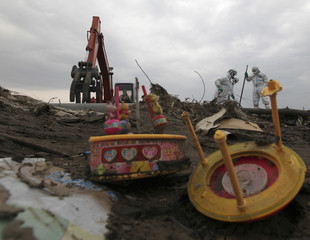 A toy is seen at a destroyed area while police officers in protective suits, search for bodies in Minamisoma