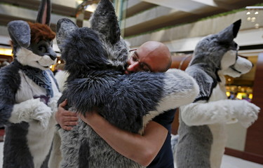 "A man is hugged by an attendee dressed up in a ""fursuit"" costume at the Midwest FurFest in the Chicago suburb of Rosemont, Illinois, United States"