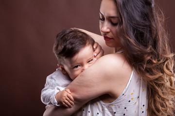 Mother and her happy little baby boy in studio photo. Motherhood and childhood