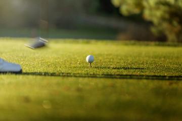 Golfer hitting iron club on golf course on fairway. Golf ball on tee.