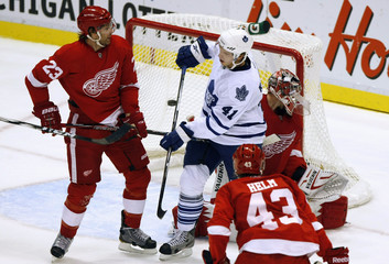 Toronto Maple Leafs' Kulemin watches the puck go into the net on a goal by teammate Gardiner against Red Wings' defenseman Stuart and goalie Howard during the first period of their NHL hockey preseason game in Detroit