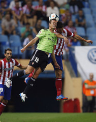 Osasuna's Riera and Atletico Madrid's Fernandez head ball during Spanish first division soccer match in Madrid