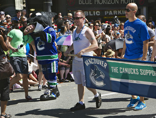 Fin the mascot for the NHL Vancouver Canucks jokes with a TV reporter while marching in the 35th Annual Gay Pride Parade with player Malhotra in Vancouver