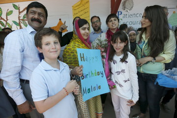 Nobel Peace Prize laureate Malala Yousafzai carries a sign commemorating her birthday at a school for Syrian refugee girls, built by the NGO Kayany Foundation, in Lebanon's Bekaa Valley