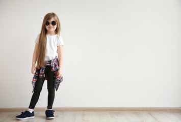 Cute little girl on light wall background. Fashion concept Wall mural