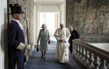 Britain's Queen Elizabeth walks with Pope Benedict XVI in the Palace of Holyroodhouse in Edinburgh