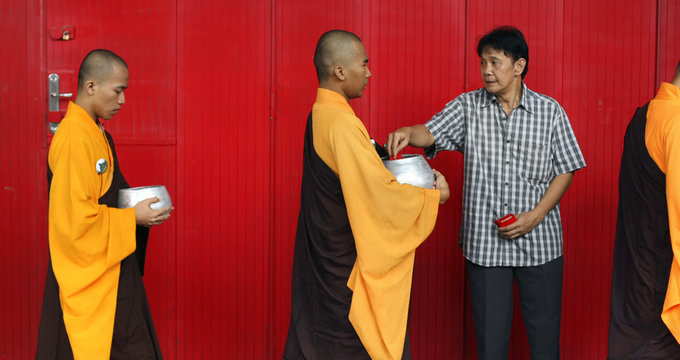 A Buddhist man gives alms to monks collecting food and money for the poor in Magelang