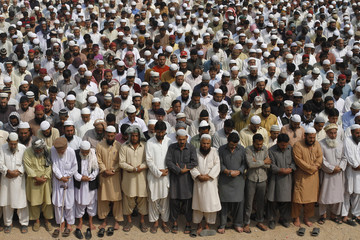Supporters of Jamiat-Ulema-e-Islam and Ahl-i-Sunnat Wal Jaaat attend funeral prayer for workers who were shot by unidentified gunmen a day earlier, in Karachi