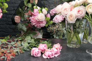 Female florist creating beautiful bouquet in flower shop, close up