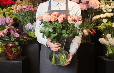 Female florist holding glass vase with roses in flower shop