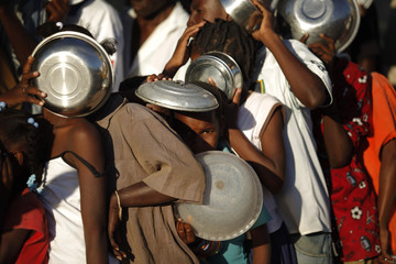 People queue to receive food by a Haitian foundation in downtown Port-au-Prince