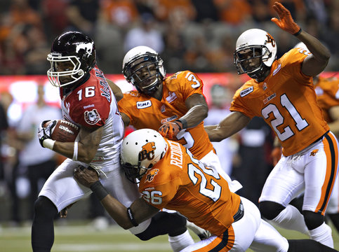 Calgary Stampeders' McDaniel is chased by BC Lions' Reddick, Muamba and Phillips during their CFL football game in Vancouver