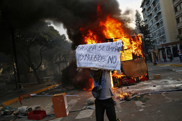 An anti-government protester holds up a banner next to a burning kiosk during a protest at Altamira square in Caracas