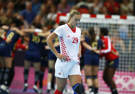 Croatia's Sonja Basic leaves the court in dejection as Spain celebrates in the background after their women's handball quarterfinals match at the Copper Box venue during the London 2012 Olympic Games