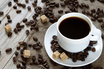 Black coffee in a mug and scattered roasted beans on wooden background