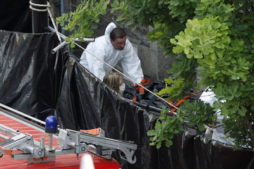 Crime scene investigators carry a stretcher from the house where human body parts were found in Nantes