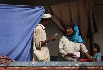 Laborer Zarsheed discusses his internally displaced person registration form with a relative in a flood field hospital in Nowshera in Pakistan's northwest Khyber-Pakhtunkhwa Province