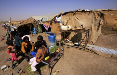 South Sudanese wait outside their tent at Andalus camp during visit by UN High Commissioner for Refugees Antonio Guterres in Khartoum