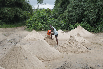 A man pours out a bucket of sand into a pile near the Lampassa river in Franceville