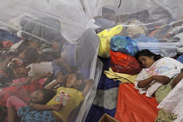 Migrants who arrived in Indonesia by boat rest inside a shelter in Kuala Langsa