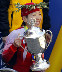 Wakako Tsuchida of Japan holds up the trophy after winning the women's wheelchair division of the 2011 Boston Marathon in Boston
