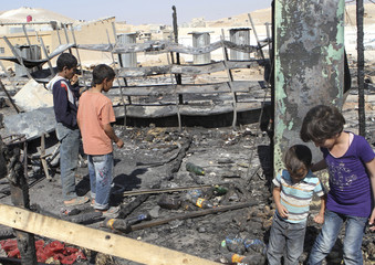 Children look at damage and the remains of tents for Syrian refugees in Arsal