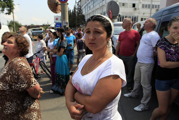 A Roma woman stands outside the house of late self-appointed Roma king Florin Cioaba during his funeral ceremony in Sibiu