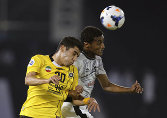 Ali of Al-Sadd fights for the ball with Sharifi of Foolad Mobarakeh Sepahan during their AFC Championship League soccer match in Doha