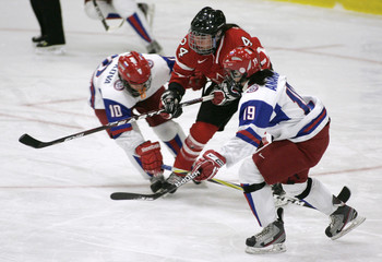 Spooner of Canada fights for puck with Belyakova and Ananina of Russia at IIHF Ice Hockey Women's World Championship in Burlington