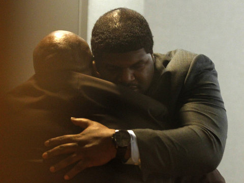 Former Dallas Cowboys player Brent embraces a man during a break in his trial in Dallas
