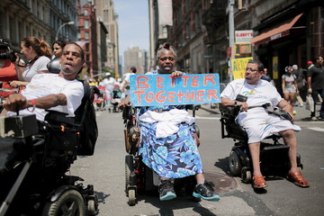 People on wheelchairs with different disabilities take part in the disability pride parade in New York