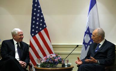 Israeli President Peres sits next to U.S. Defense Secretary Gates at their meeting in Tel Aviv