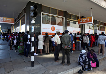 Zimbabweans queue to withdraw cash, at money transfer agency in the capital Harare
