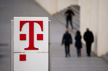 People walk past the logo of German telecommunications giant Deutsche Telekom AG seen at the Telekom's headquarters in Bonn
