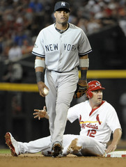 New York Yankees' Cano walks away after tagging out St. Louis Cardinals' Berkman during Major League Baseball's All-Star Game in Phoenix