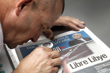 A man inspect the front page of the French daily morning newspaper Liberation at their printing press in La Courneuve