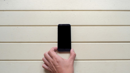 Wall Mural -  smart phone with hand topview on wood background