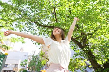 若い女性 新緑の公園で背伸びをするイメージ