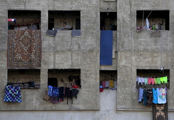 People stand beside hanged clothing at a compound housing Syrian refugees in Sidon, southern Lebanon
