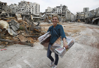 A woman reacts to the camera as she carries some items from her home following the cessation of fighting between rebels and forces loyal to Syria's President Bashar al-Assad at al-Hamdeya neighborhood in Homs city