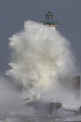 Waves crash against a lighthouse as the wind blows at around 100 kph (62 mph), in Boulogne-sur-Mer