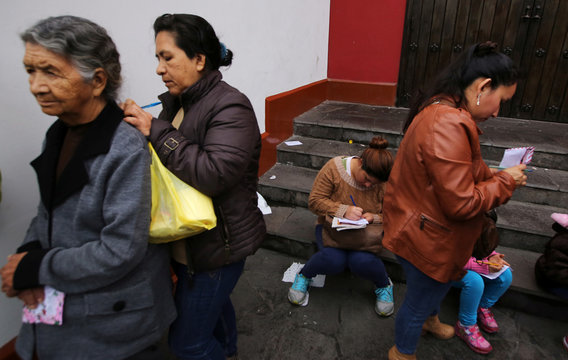People write letters before throwing them into the well of wishes at Saint Rose's Church during celebrations of the anniversary of Santa Rosa de Lima in Lima