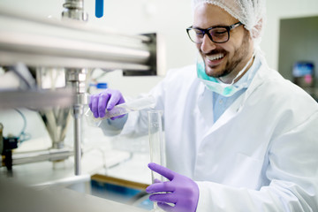 Smiling lab technician doing water analysis, dressed in protective sterile equipment.